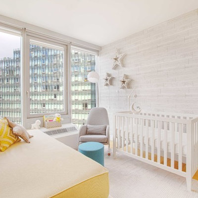 Example of a small trendy gender-neutral light wood floor and brown floor nursery design in New York with gray walls