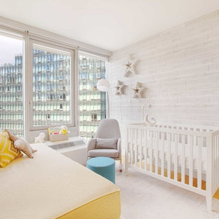 Small contemporary gender neutral nursery in New York with grey walls, light hardwood flooring and brown floors.