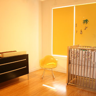 Inspiration for a mid-sized gender-neutral bamboo floor nursery remodel in St Louis with yellow walls