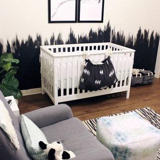 Diseño de habitación de bebé niño moderna, de tamaño medio, con paredes blancas, suelo de madera en tonos medios y suelo marrón