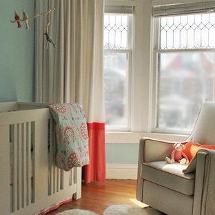 Photo of a medium sized bohemian nursery for girls in Toronto with blue walls and medium hardwood flooring.