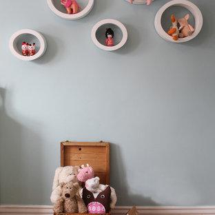 Ejemplo de habitación de bebé niña bohemia, de tamaño medio, con paredes azules y suelo de madera en tonos medios