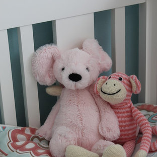 This is an example of a medium sized eclectic nursery for girls in Toronto with blue walls and medium hardwood flooring.