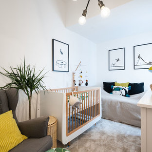 Inspiration for a contemporary gender neutral nursery in London with white walls, carpet and beige floors.