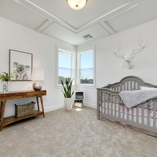 Mid-sized farmhouse gender-neutral carpeted and beige floor nursery photo in Boise with white walls