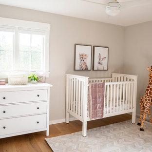 Modelo de habitación de bebé niña de estilo de casa de campo, pequeña, con paredes beige y suelo de madera clara