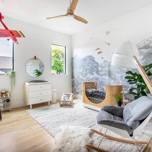 Diseño de habitación de bebé neutra actual con paredes blancas, suelo de madera clara y suelo beige