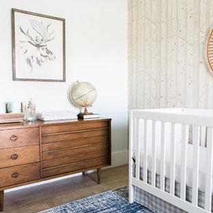 Diseño de habitación de bebé niño tradicional renovada, pequeña, con paredes beige y suelo de madera clara