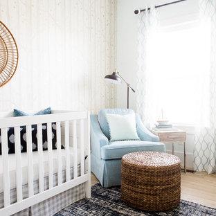 Ejemplo de habitación de bebé niño clásica renovada, pequeña, con paredes beige y suelo de madera clara