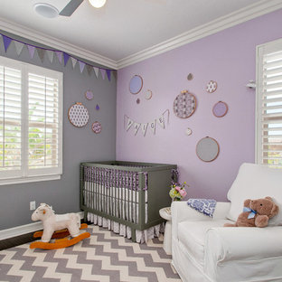 Exemple d'une chambre de bébé fille chic de taille moyenne avec un mur violet et un sol en bois foncé.