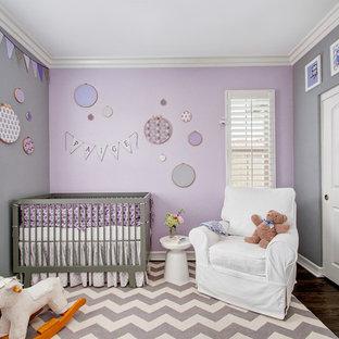 Ejemplo de habitación de bebé niña tradicional renovada, de tamaño medio, con paredes púrpuras y suelo de madera oscura