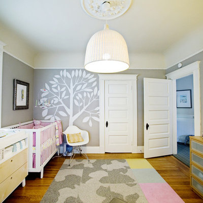 Example of a mid-sized transitional girl medium tone wood floor nursery design in San Francisco with gray walls