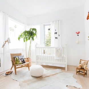 Nursery - mid-sized modern girl light wood floor and beige floor nursery idea in Los Angeles with white walls