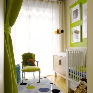Ejemplo de habitación de bebé neutra actual, pequeña, con paredes verdes y suelo de bambú