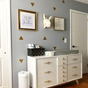 Cette photo montre une petit chambre de bébé garçon scandinave avec un mur gris et un sol en bois brun.