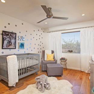 Imagen de habitación de bebé neutra tradicional renovada con paredes multicolor, suelo de madera en tonos medios y suelo naranja