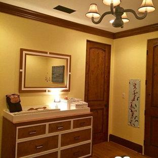 Aménagement d'une chambre de bébé neutre contemporaine avec un mur jaune et un sol en bois brun.