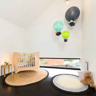 Photo of a mid-sized contemporary gender-neutral nursery in Melbourne with white walls, dark hardwood floors and black floor.