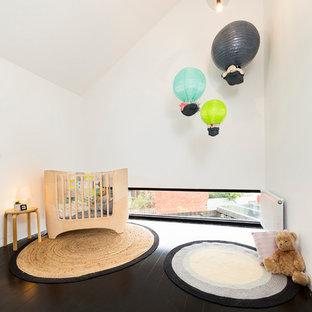 Imagen de habitación de bebé neutra contemporánea, de tamaño medio, con paredes blancas, suelo de madera oscura y suelo negro
