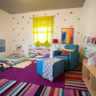 Example of a large eclectic girl medium tone wood floor and multicolored floor nursery design in San Diego with beige walls