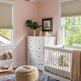 Imagen de habitación de bebé niña clásica renovada con paredes rosas, suelo de madera en tonos medios y suelo marrón