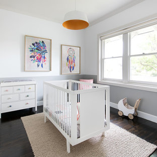 This is an example of a mid-sized transitional nursery for girls in Melbourne with multi-coloured walls, dark hardwood floors and brown floor.