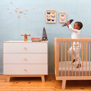 Imagen de habitación de bebé neutra tradicional renovada, pequeña, con paredes azules y suelo de madera en tonos medios