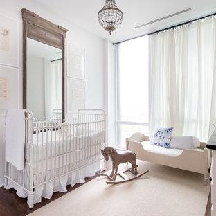 Modelo de habitación de bebé niña clásica renovada, grande, con paredes blancas, suelo de madera oscura y suelo marrón