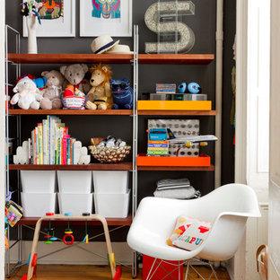 Ejemplo de habitación de bebé neutra ecléctica con paredes negras, suelo de madera en tonos medios y suelo naranja