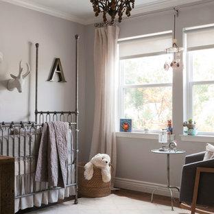 Ejemplo de habitación de bebé neutra tradicional renovada con paredes grises y suelo de madera en tonos medios