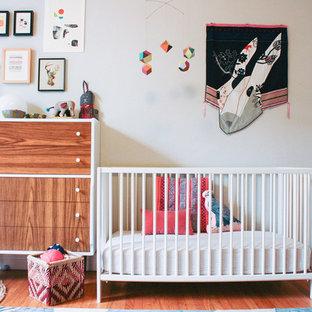 Imagen de habitación de bebé niña bohemia, pequeña, con paredes blancas y suelo de madera en tonos medios