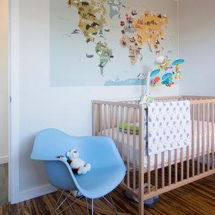 Réalisation d'une chambre de bébé neutre vintage avec un mur gris et un sol en bois foncé.