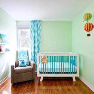 Esempio di una piccola cameretta per neonati minimal con pareti verdi e pavimento in legno massello medio
