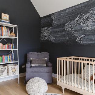 Cette image montre une chambre de bébé neutre nordique avec un mur noir, un sol en bois clair et un plafond voûté.