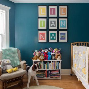 Modelo de habitación de bebé neutra clásica renovada con suelo de madera en tonos medios, paredes azules y suelo beige