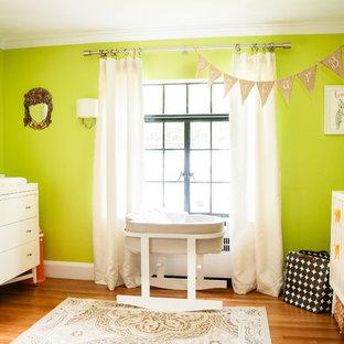 Réalisation d'une chambre de bébé neutre design avec un mur vert, un sol en bois brun et un sol orange.