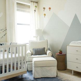 Ispirazione per una cameretta per neonato contemporanea di medie dimensioni con pareti beige e pavimento in legno massello medio