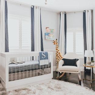 Imagen de habitación de bebé niño moderna, de tamaño medio, con paredes blancas, suelo de madera oscura y suelo blanco