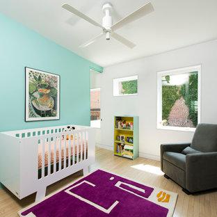 Foto de habitación de bebé neutra nórdica, de tamaño medio, con paredes azules, suelo de madera clara y suelo beige