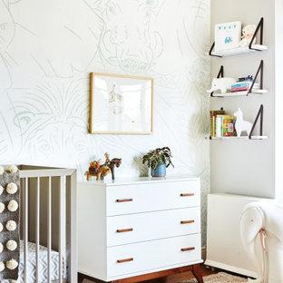 Esempio di una cameretta per neonati chic con pareti bianche, pavimento in legno massello medio, pavimento marrone e carta da parati