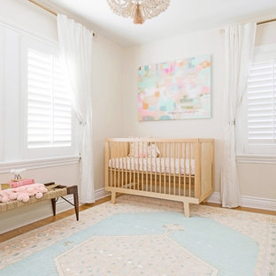Inspiration for a small bohemian nursery for girls in Los Angeles with beige walls and light hardwood flooring.