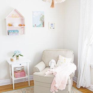 Imagen de habitación de bebé niña ecléctica, pequeña, con paredes beige y suelo de madera clara