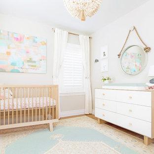 Imagen de habitación de bebé niña tradicional renovada, pequeña, con paredes beige y suelo de madera clara