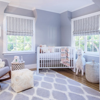 Example of a large transitional girl medium tone wood floor and brown floor nursery design in San Francisco with purple walls
