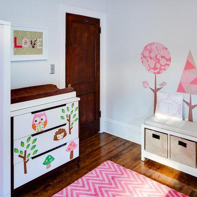 Trendy girl dark wood floor nursery photo in Minneapolis with white walls