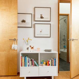Cette image montre une petit chambre de bébé neutre nordique avec un mur blanc, un sol en bambou et un sol beige.