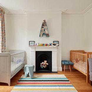 Imagen de habitación de bebé neutra clásica renovada, grande, con paredes blancas, suelo de madera en tonos medios y suelo multicolor