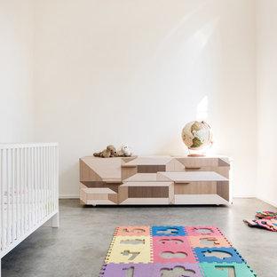 Cette image montre une chambre de bébé neutre minimaliste de taille moyenne avec un mur beige, béton au sol et un sol gris.