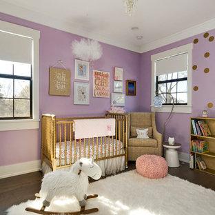 Réalisation d'une grand chambre de bébé fille tradition avec un mur violet et un sol en bois foncé.