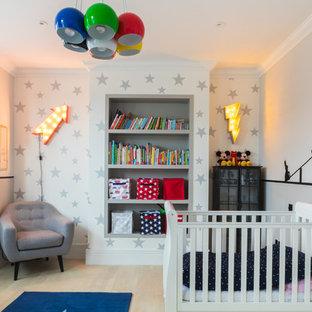 Foto de habitación de bebé neutra tradicional renovada con paredes grises, suelo de madera clara y suelo beige